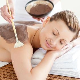 Relaxed woman enjoying a mud skin treatment